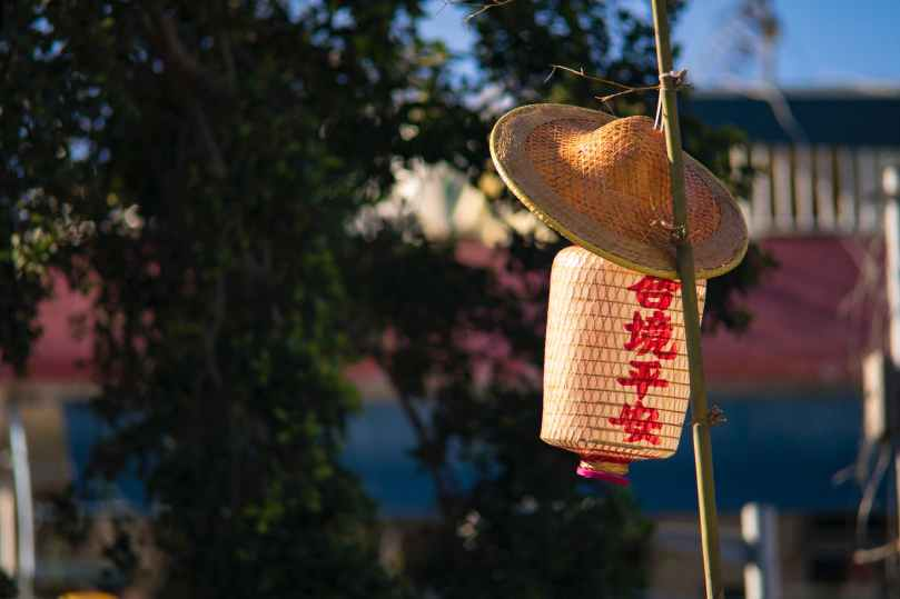 straw hat and paper lantern placed on bamboo pole